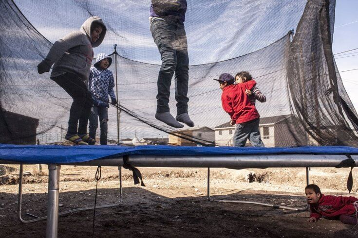 A few children jumping on a trampoline