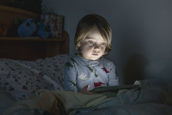child looking at at screen in bed