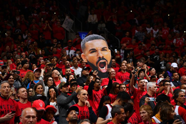A crowd of Raptors fans holding a cutout of Drake's head.