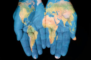 Photo of a person's hands with a map of the world drawn on it