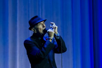 Leonard Cohen performing in front of a blue curtain