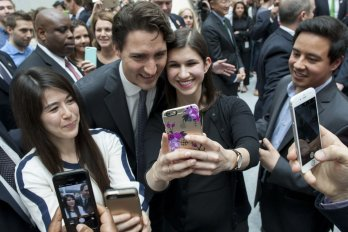 A couple of women taking selfies with justin trudeau
