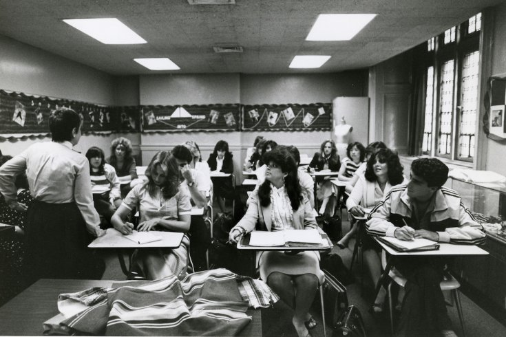 Several college students at desks in classroom
