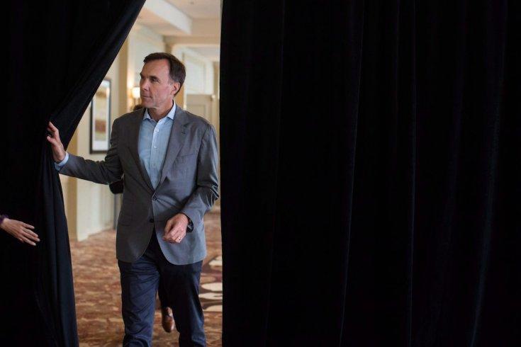 man opening up black curtain to walk through