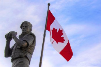 statue of peacekeeper in front of Canadian flag
