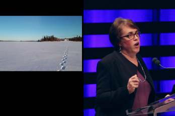 Woman speaking at walrus talks beside photograph of footprints in the snow