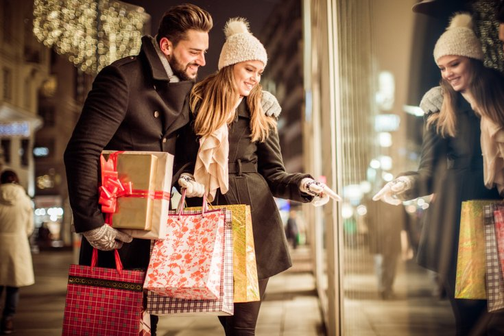white couple amassing gifts for christmas look through shop window