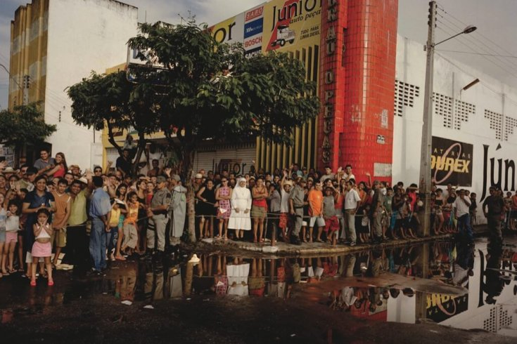 People standing in a line on a wet road in sobral