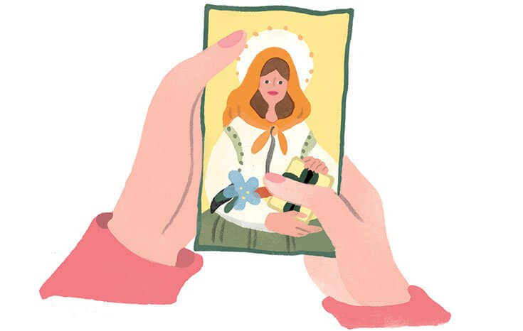 A woman's hands holding a picture of a saint.