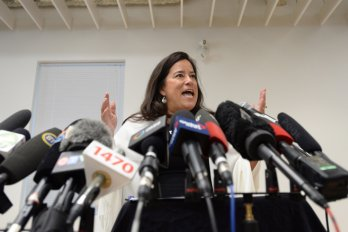 Jody Wilson-Raybould speaking into a crowd of media microphones