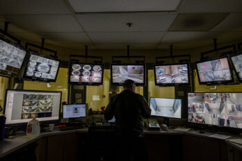 An officer at the Cameron County Detention Centre watches security footage from the control room, on many screens.