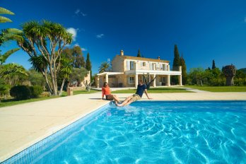 A man and a woman sit on the edge of a large pool with their legs in the water; behind them is an elaborate villa against a backdrop of trees and a blue sky.