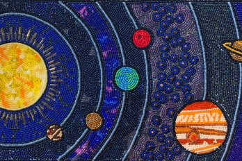 Beadwork of concentric rings of the solar system, with the sun in the center and planets surrounding it.