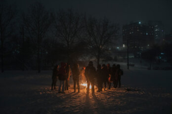 Photo of a group of people gathered in a circle around a fire put, after sundown.
