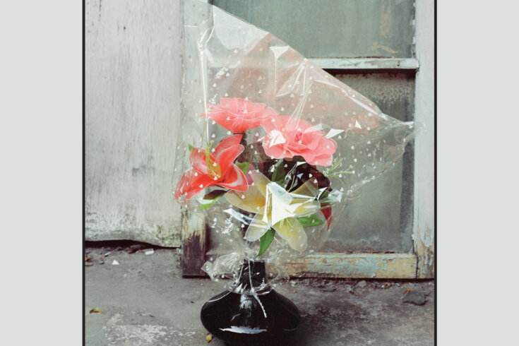 Photograph of pink flowers in a black ceramic vase on a shabby concrete floor.