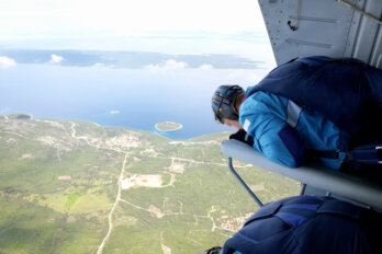 A photograph of skydivers waiting at the edge of an open helicopter door before making the jump.
