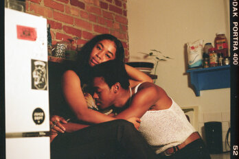 A Black man embraces a Black woman who is sitting on a kitchen countertop. The woman is looking at the camera.
