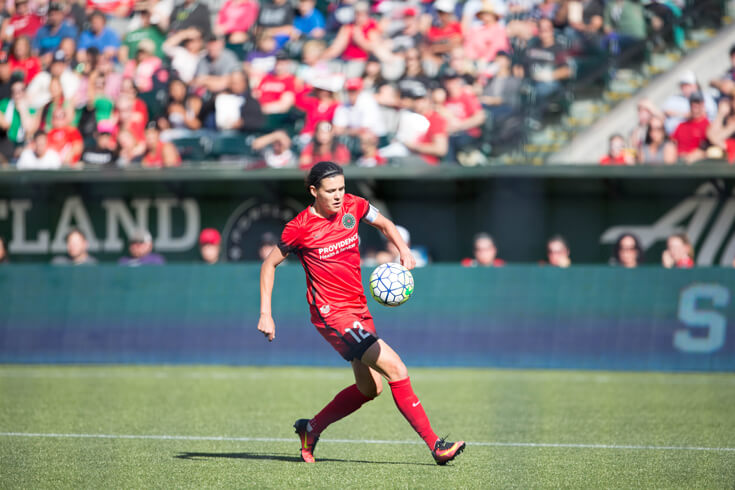Christine Sinclair runs on the soccer field.