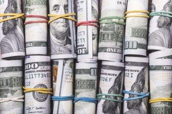 Rolls of American bills bound with coloured elastics