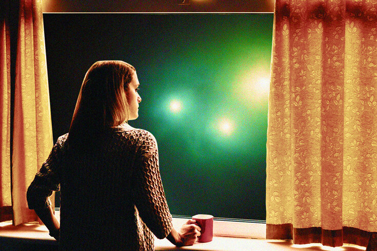 A woman stares out of a window at a night sky with UFOs.