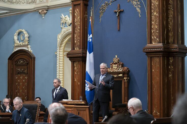 A man speaks on a stage at the Quebec Legislature with a crucifix over his head on the dark blue wall behind him.