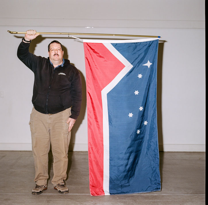 A man wearing a fleece and corduroy pants holds a flag designed for the Western Independence Party in the 1980s. The top two thirds are blue, with half a dozen stars. The lower third is red. The colours are bisected by a jagged white line.