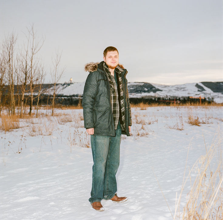 A young bearded man wearing jeans and a winter coat and a plaid shirt stands outdoors in the snow.