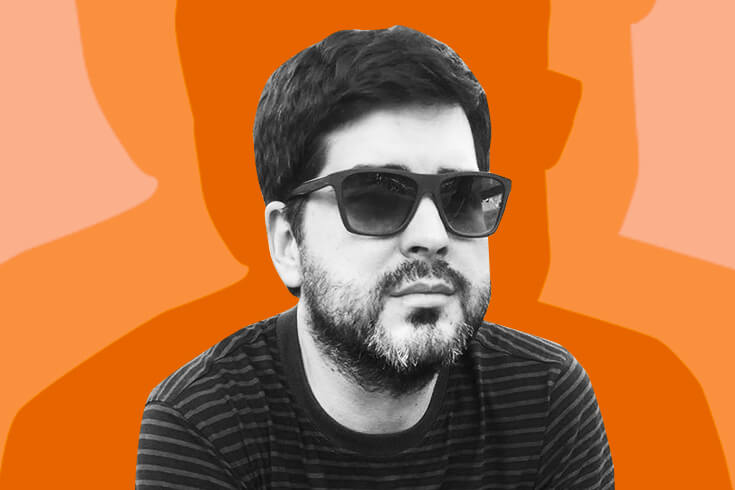 A photograph of the poet, a dark-haired bearded man wearing sunglasses and smiling, against a bright orange background.