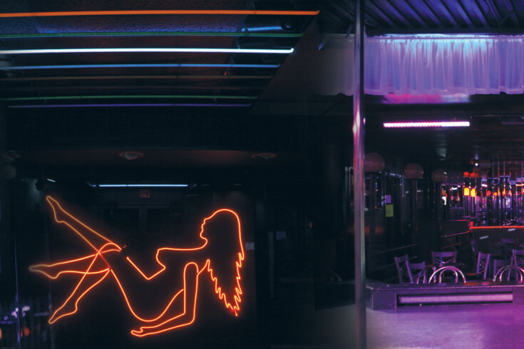 Empty strip club with a neon sign depicting the silhouette of a woman dancing