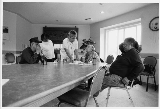 Lillian Moyer serves supper to Edith Carlick in the conference room of the Telegraph Creek band office. Lucy Brown stands at left, next to her husband Orville. Pat Carlick is seated at right.