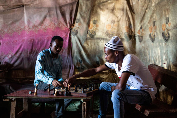 Two men play chess inside an Ethiopian restaurant, the walls covered by patterned cloths..