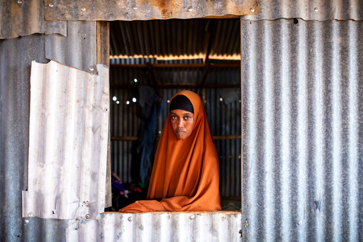 A woman in an orange hijab, staring out of an open window in a metal structure.