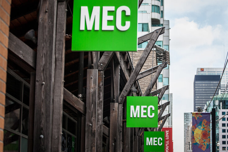 """A photograph of the wooden exterior of the downtown Toronto MEC location, with the green """"MEC"""" sign displayed outside."""