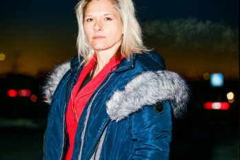 A photograph of a blonde woman staring seriously into the camera. She is outside in the evening and wearing a blue winter coat over a red zip-up sweatshirt.