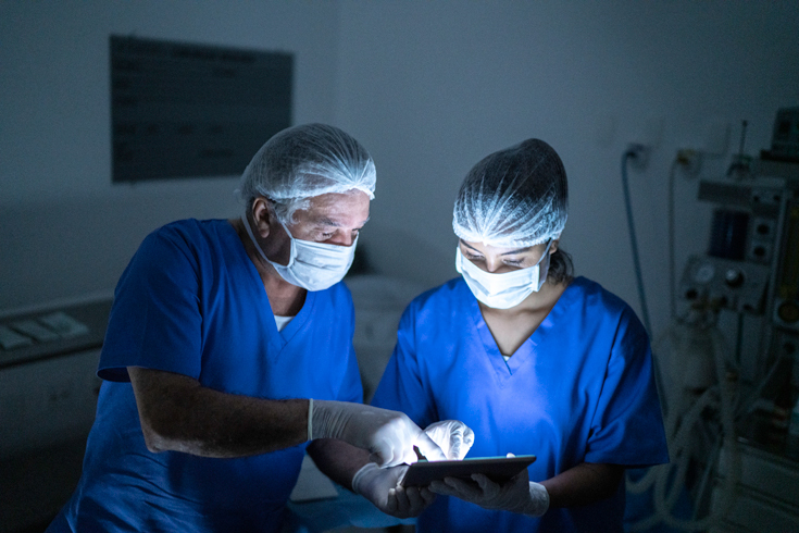 A photograph of two doctors in masks and scrubs staring down at a lit screen in a dim room.