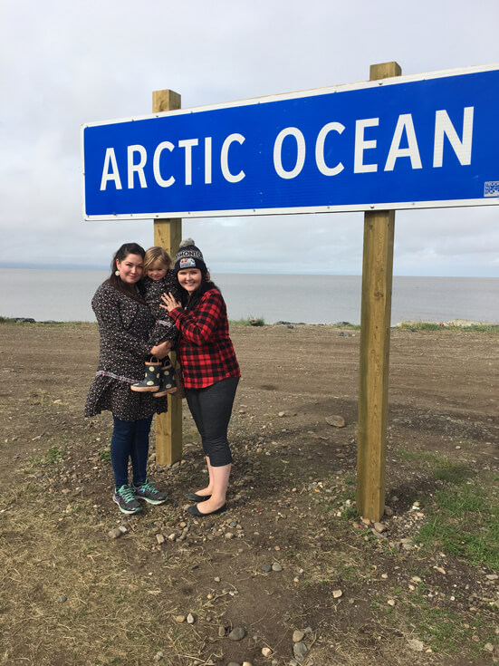 "Two women and a toddler huddle together beneath a sign that reads ""Arctic Ocean."""