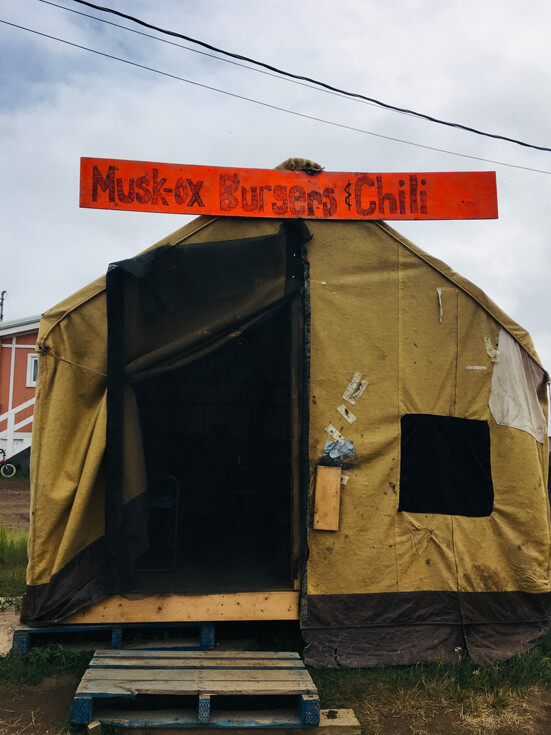"""An open brown tent with a hand-drawn red sign that is advertising """"Musk-ox burgers and chili."""""""