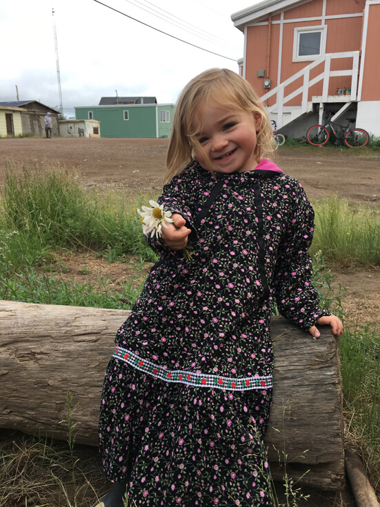 A toddler with long blonde hair in a floral printed dress holds a daisy to the camera and smiles.