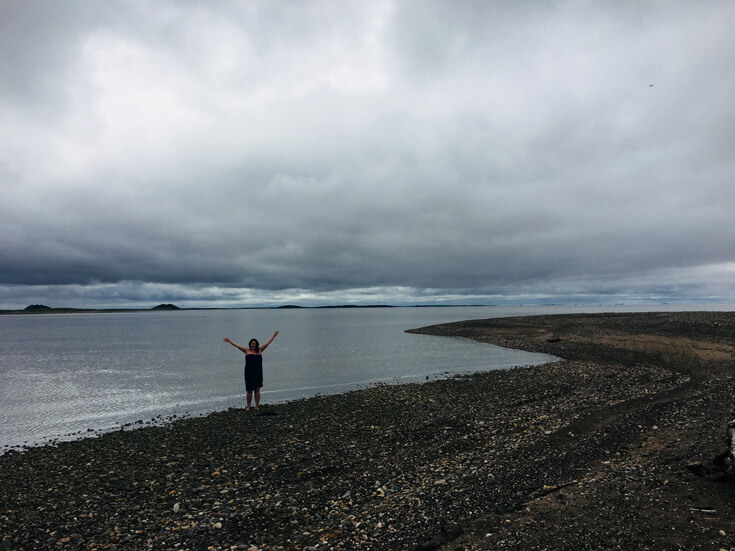 A woman stands on the rocky shore of a beach and raises her arms against a backdrop of water and a grey sky.