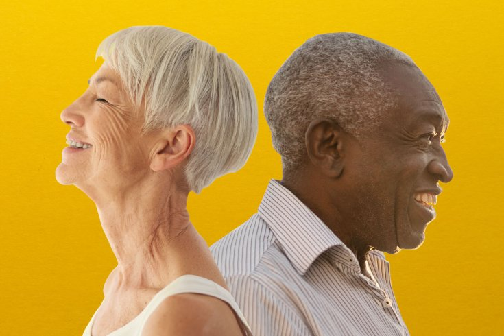 Two elderly people standing together but facing opposite directions