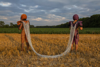 Two Black men stand in a harvested field under a cloudy sky. They are dressed in football uniforms printed with colourful African textiles. They are standing apart and facing away from each other, attached by a set of chains on their backs.