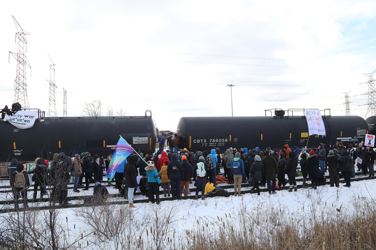 A small crowd of protesters, Shut Down Canada, stand along the train tracks and occupy the Macmillan Yard in Vaughan, Ontario. In front of them is a large black train.