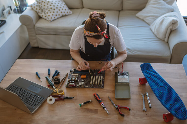 A photo of a woman working on various electronics