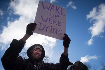 "A man holds up a protest sign that says ""Wake up we're dying."""