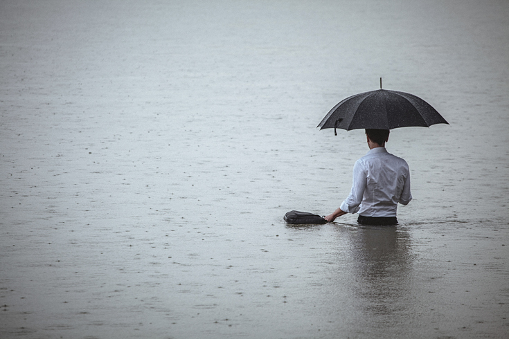 Rear view of a man wearing white shirt and holding an umbrella and a briefcase, standing waist-deep in the water on a rainy day