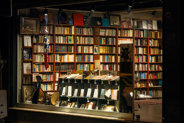 A photograph of the exterior of a bookstore at nighttime. Inside, the store is lit and the shelves are full.