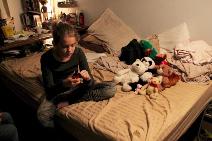 Vanda sits with the girls' stuffed-animal collection in their living room, which doubles as the parents' bedroom. May 2016.