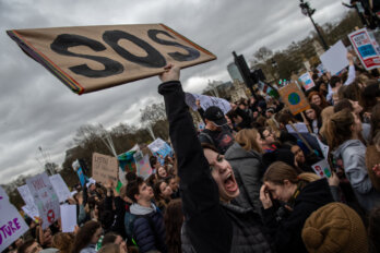 """A woman protests at a climate change demonstration holding an """"SOS"""" sign."""