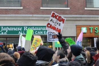 Man holding up anti-racism sign at protest in Toronto