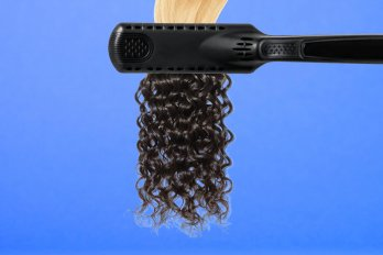 Curling iron with blonde hair on one side and curly black hair on the other